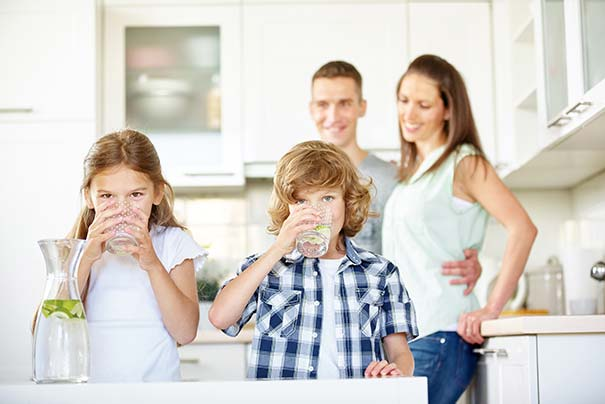 Reno Nevada Residential drinking water with parents behind 2 kids drinking clean pure filtered water from whole home water filter