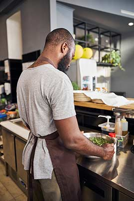 Man washing salad in restaurant using reverse osmosis purified water from food service water treatment in Reno, Nevada by Culligan