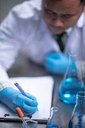 Healthcare hospital lab technician writing on tablet with beaker of chemicals made with purified water from Culligan Nevada