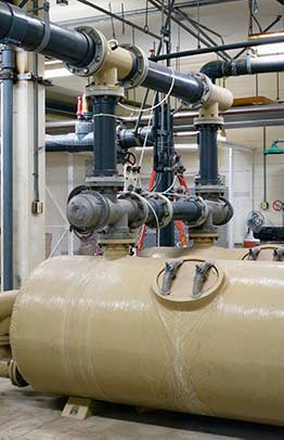 Chemical processing plant inside with large tanks and a fan in the background in Nevada